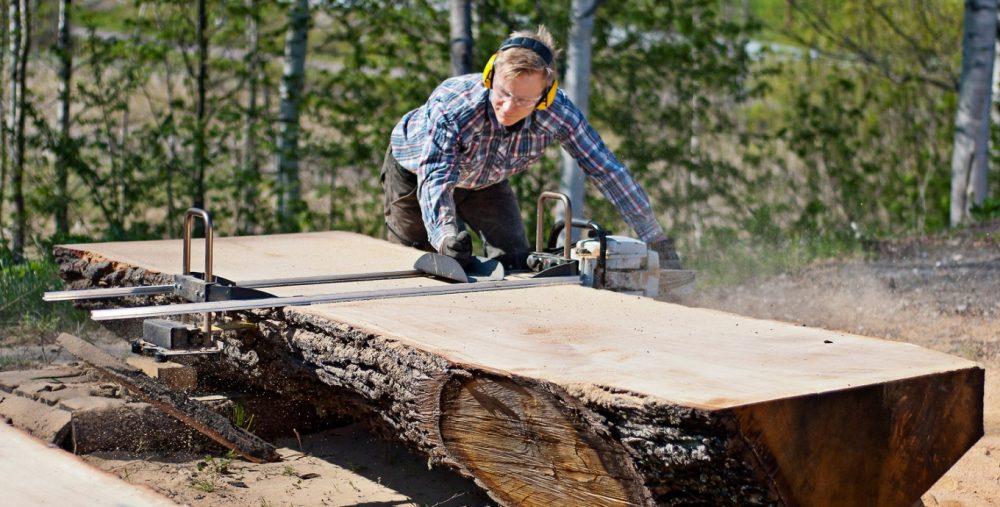 homem cortando tronco
